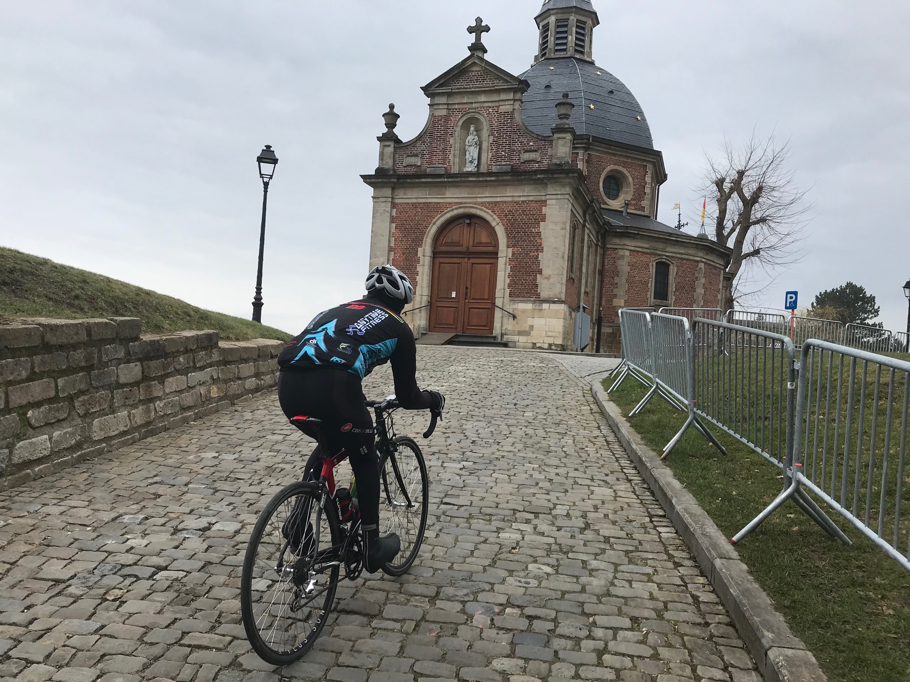 BiciSport in Flanders 18 @ 26 Mar - Mike Lawson, having climbed the first Muur, then climbs the Chapel Muur cobbled climb with the lovely Church at the summit.