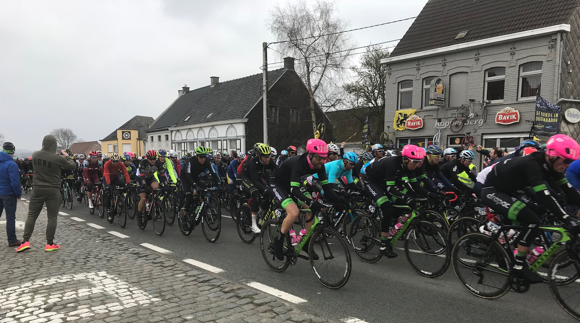 BiciSport in Flanders 18 @ 1 Apr - the Ronde Men's peloton passes the Koppenberg Cafe at Melden through the race Feeding Zone.