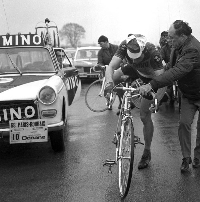 Eddy Merckx @ Paris Roubaix getting a bike change with the assistance of Lomme Driessens (Faemino Team Manager). The Peugeot 404 is the Feamino team car of choice.