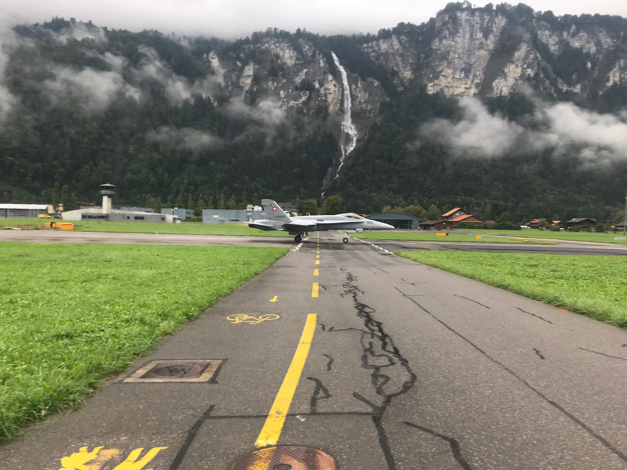 """Photo of 2018 by Peter Budd (BiciSport Master) … driving through Switzerland on a """"public road + cycle path"""" when along comes a Swiss Air Force plane taxing into a nearby underground hangar. Nice bike path !"""