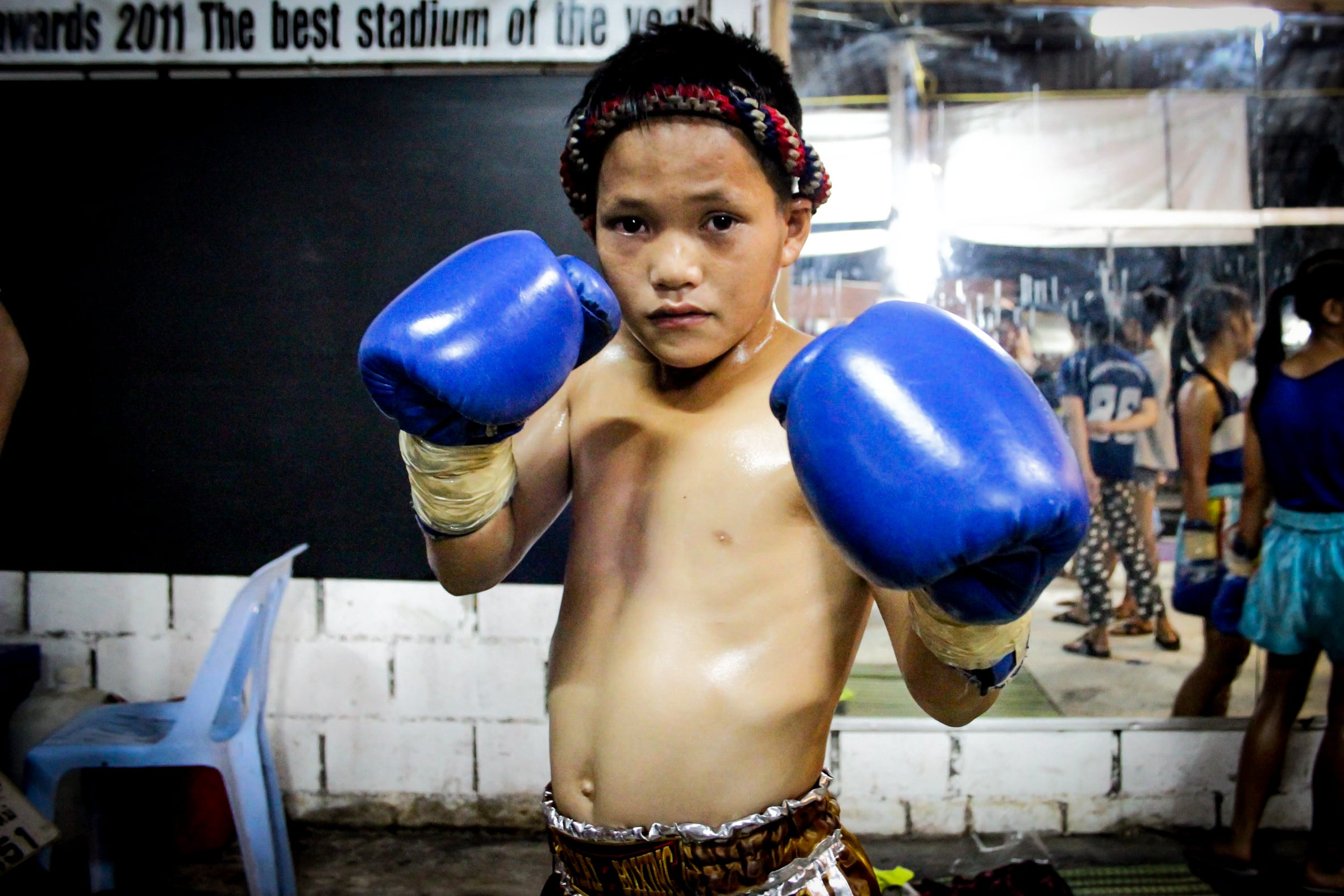 Many children are recruited to start practicing Muay Thai from as young as seven years old. As trainers, spectators and gamblers watch, they fight to win glory for their gym and prize money. For many children and their families, Muay Thai is often seen as an escape from poverty.Chiang Mai, Thailand.