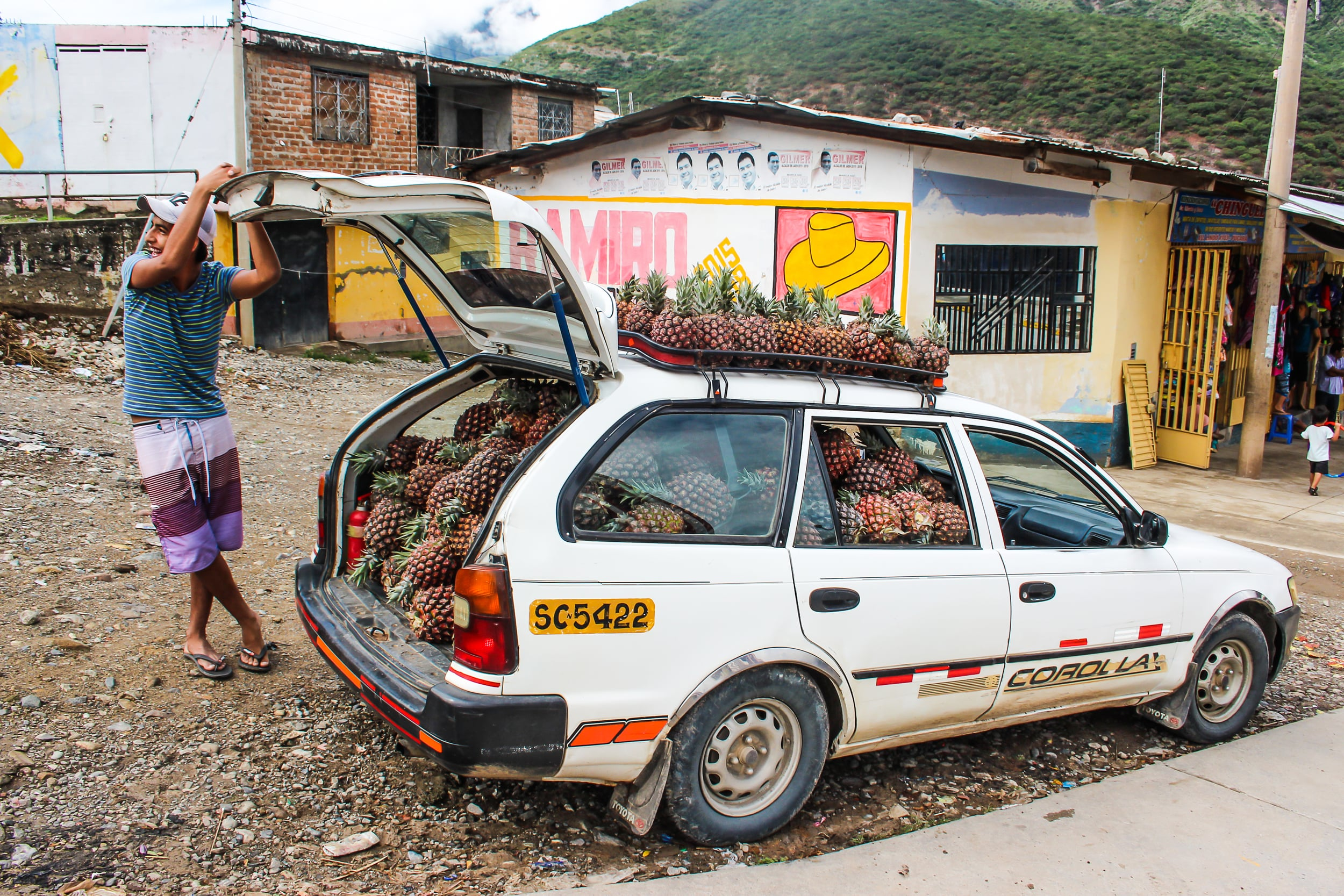 A pineapple vender takes advantage of a seven hour delay on a busy highway connecting the Amazon and the coast in Perú.    The road was blocked by debris that fell during heavy rain next to the small roadside town of Pucará. Throughout Perú, many roads collapsed or closed due to extreme weather during the rainy season in 2015.