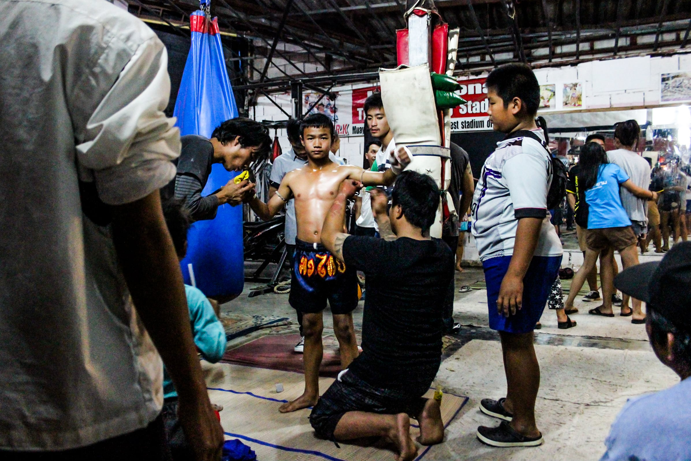 Many children are recruited to start practicing Muay Thai from as young as seven years old. As trainers, spectators and gamblers watch, they fight to win glory for their gym and prize money. For many children and their families, Muay Thai is often seen as an escape from poverty.