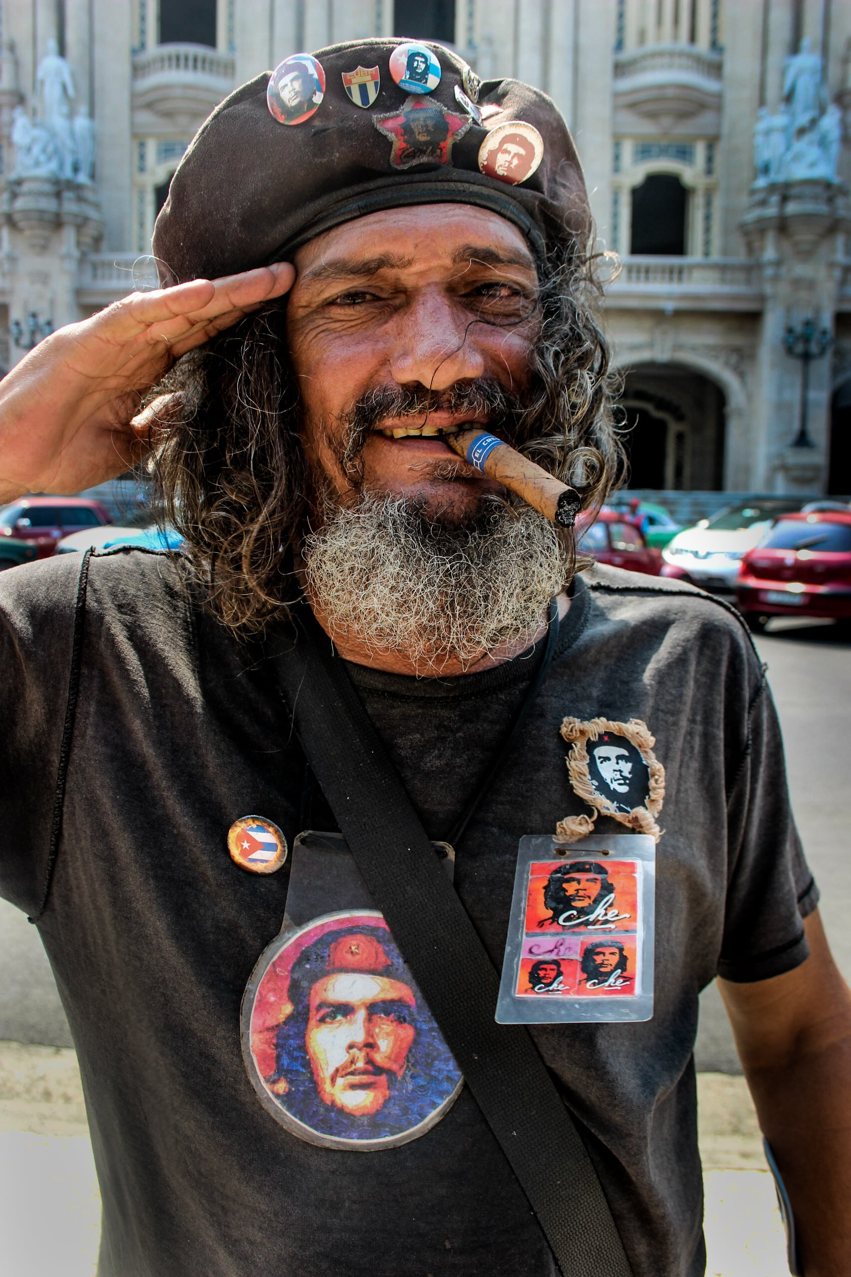 """Man makes his living charging tourists for photos while he poses with a cigar and pictures of national revolutionary icon, Ernesto """"Ché"""" Guevara.    In Cuba, salaries are fixed by the government and people are provided monthly goods rations. Working in tip-based tourism (taxi drivers, bicycle tour guides, hotel lobbyists) will often earn Cubans a higher income compared to that of a doctor or engineer.    The picture earned this gentleman 1CUP (1 US dollar)."""