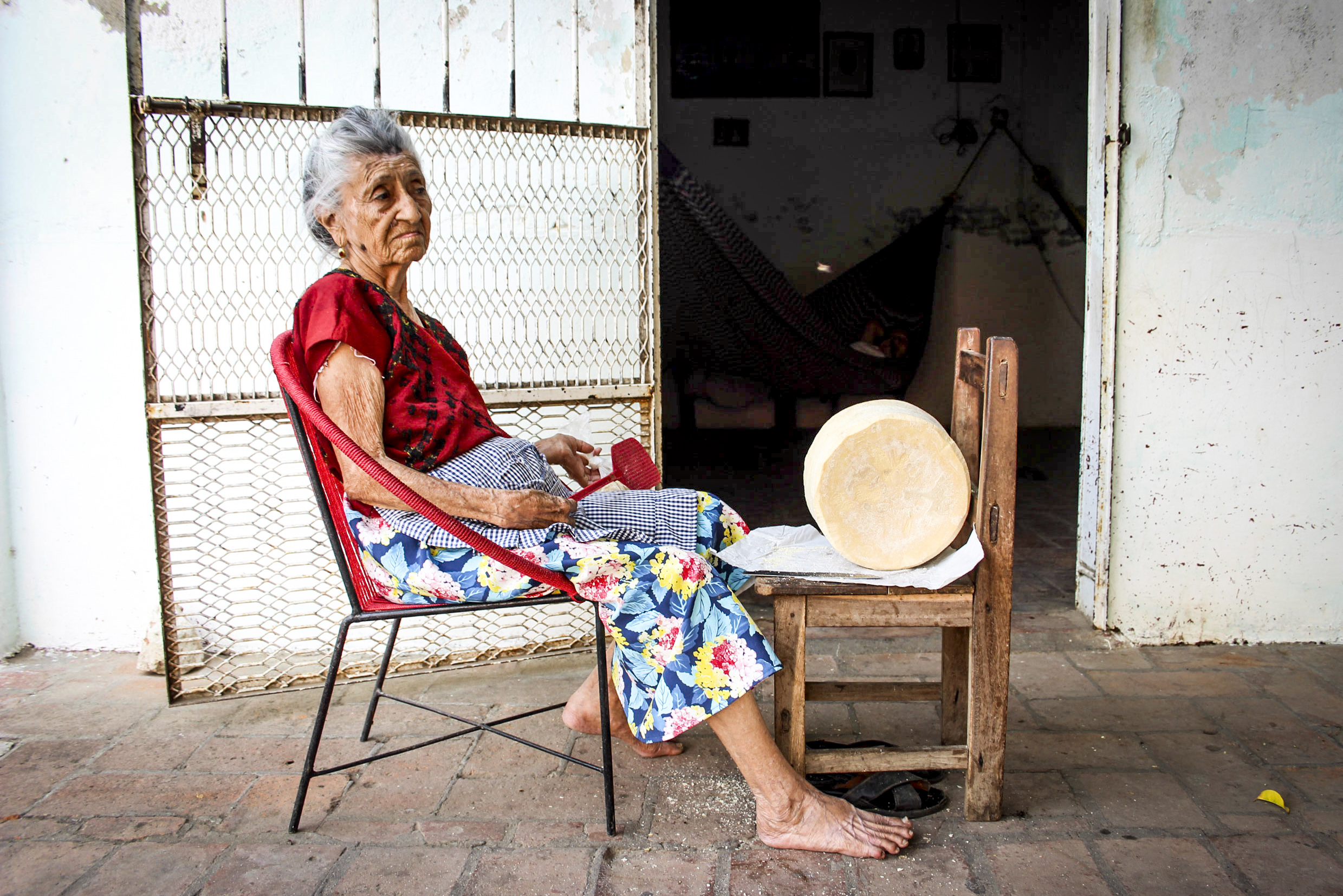 A woman spends the afternoon preparing and swatting flies from her homemade cheese in the small village of Unión Hidalgo, Méxcio. She plans to sell her handcrafted product at the markets the following morning.