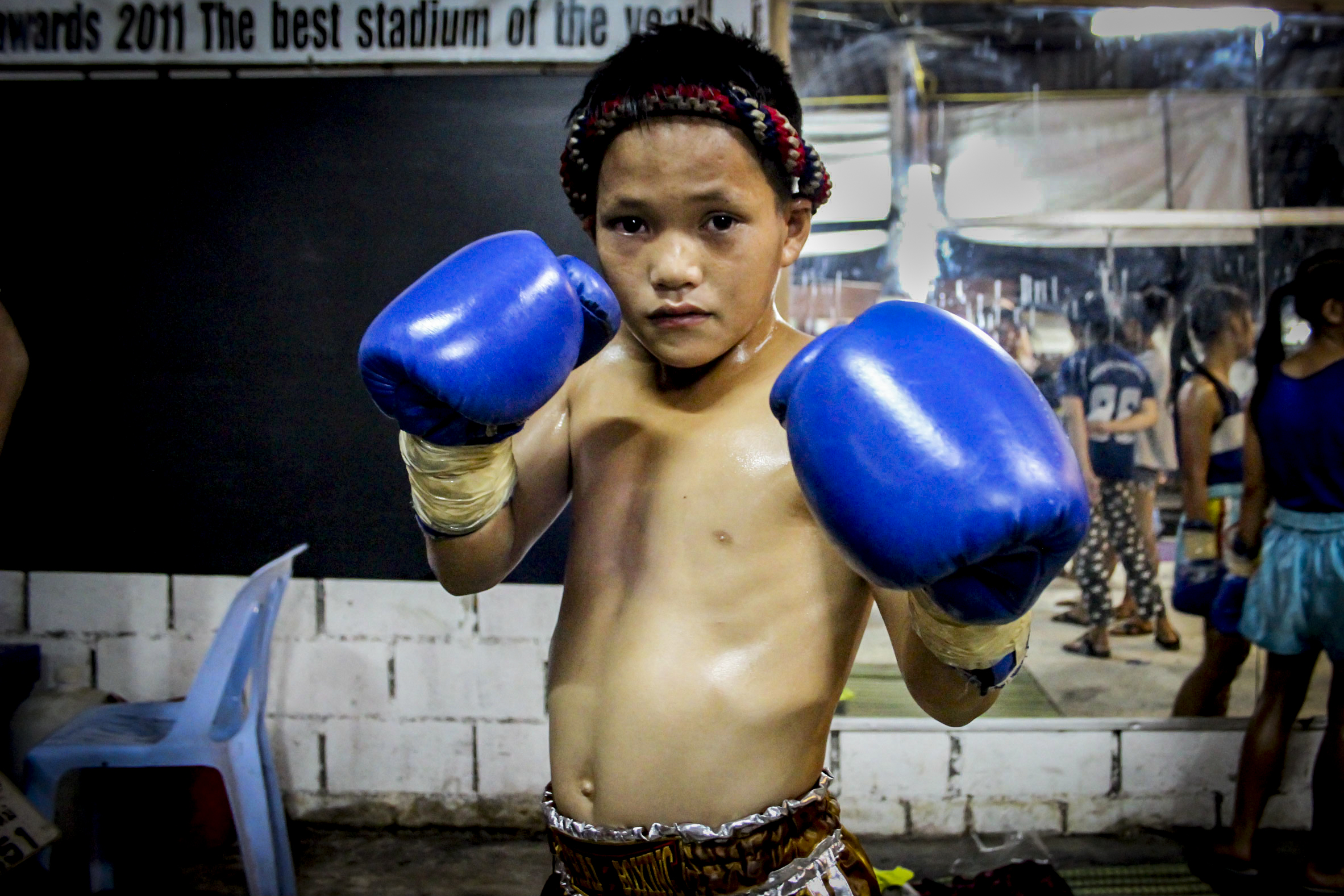 A young boy before his fight. In Thailand, many children are recruited to start practicing Muay Thai from as early as seven years old. For children and their families, Muay Thai is often seen as a way out of poverty.