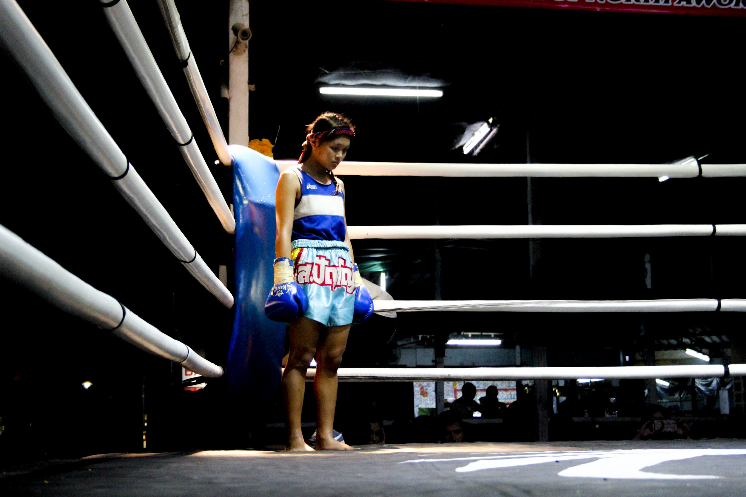 The teenage girl stands in the corner of the ring just before her fight.