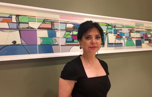 Karen stands in front of a composite photograph of all nine paintings together.