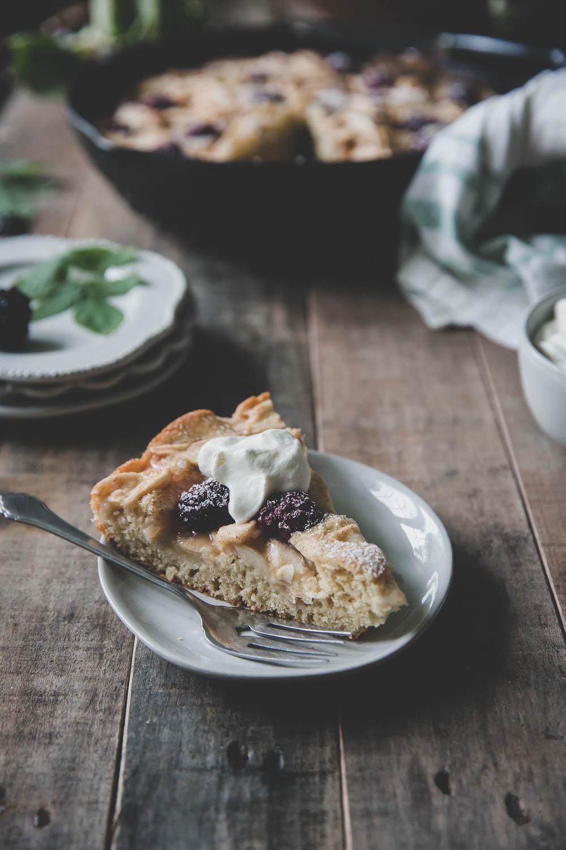 Slice of apple blackberry skillet cake, ready to eat
