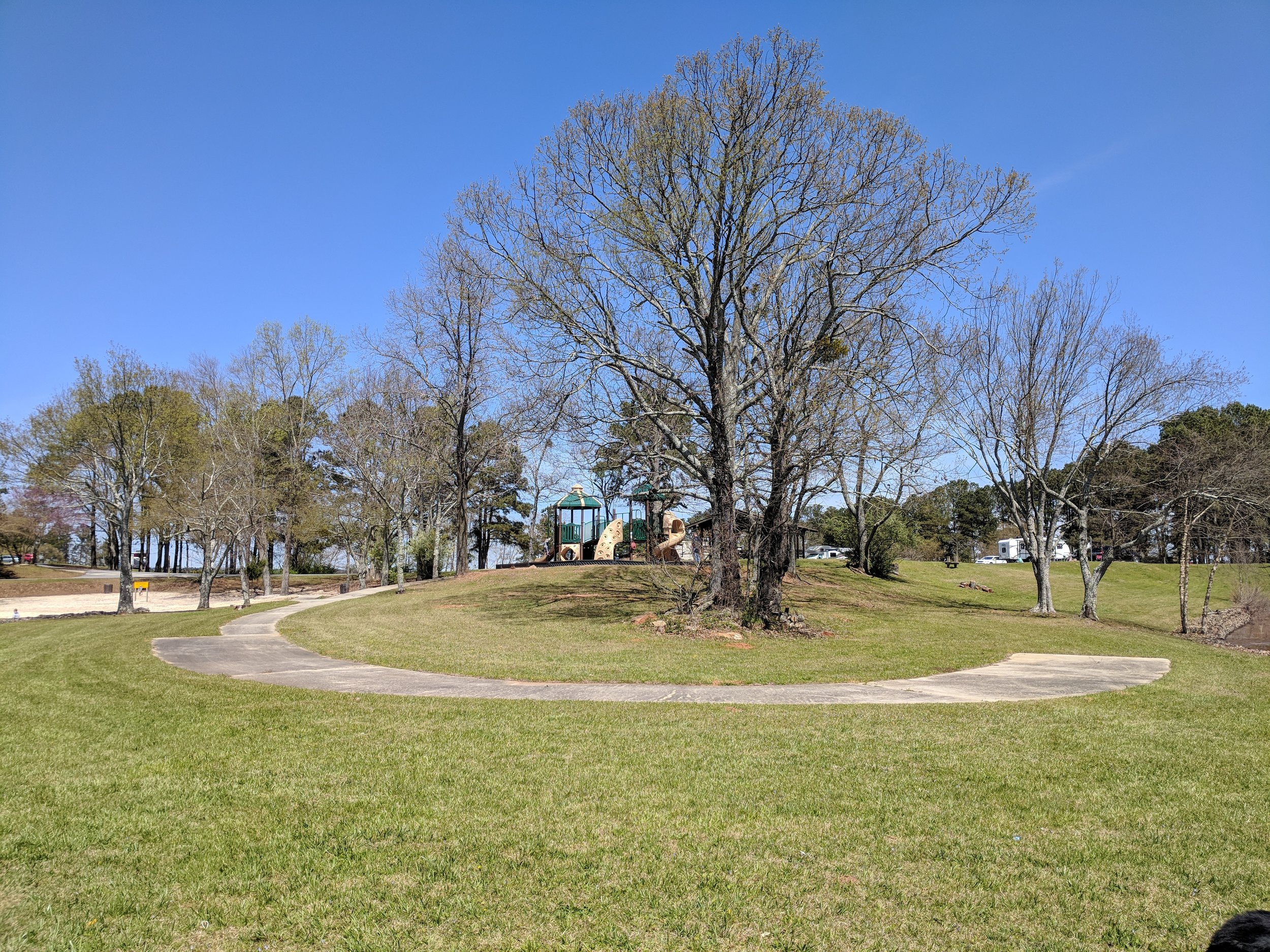 The sandy public beach area is to the left of the playground