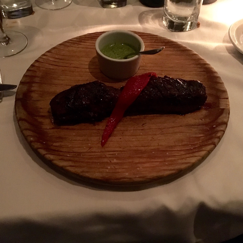 Simple elegance. Our preferred Vacio a la Gaucho (Hangar Steak) is served on a wooden plate with chimichurri sauce and a simple garnish.