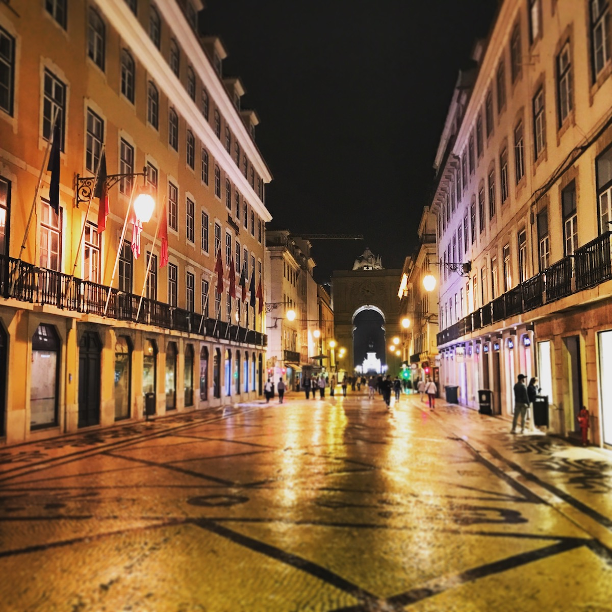 The length of Rua Augusta is paved with polished stone tiles arranged in patterns for an incredible image under the street lights. The arch marks the southern end just before the waterline.