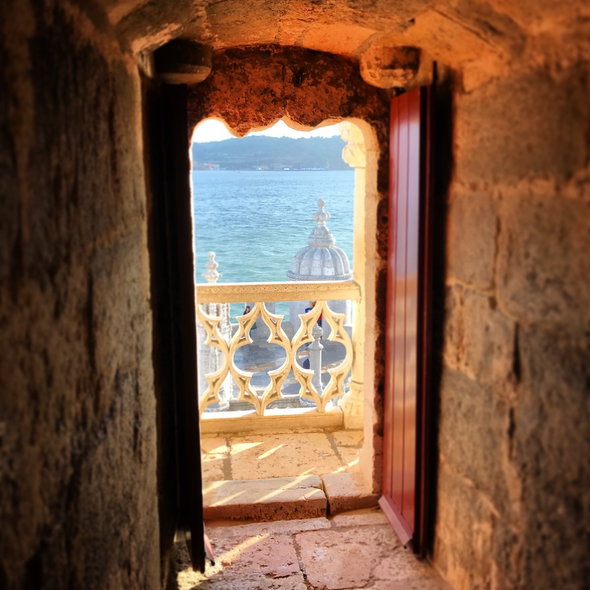 Through a door in Belém Tower, looking out to the harbor soaked in the late afternoon sun.