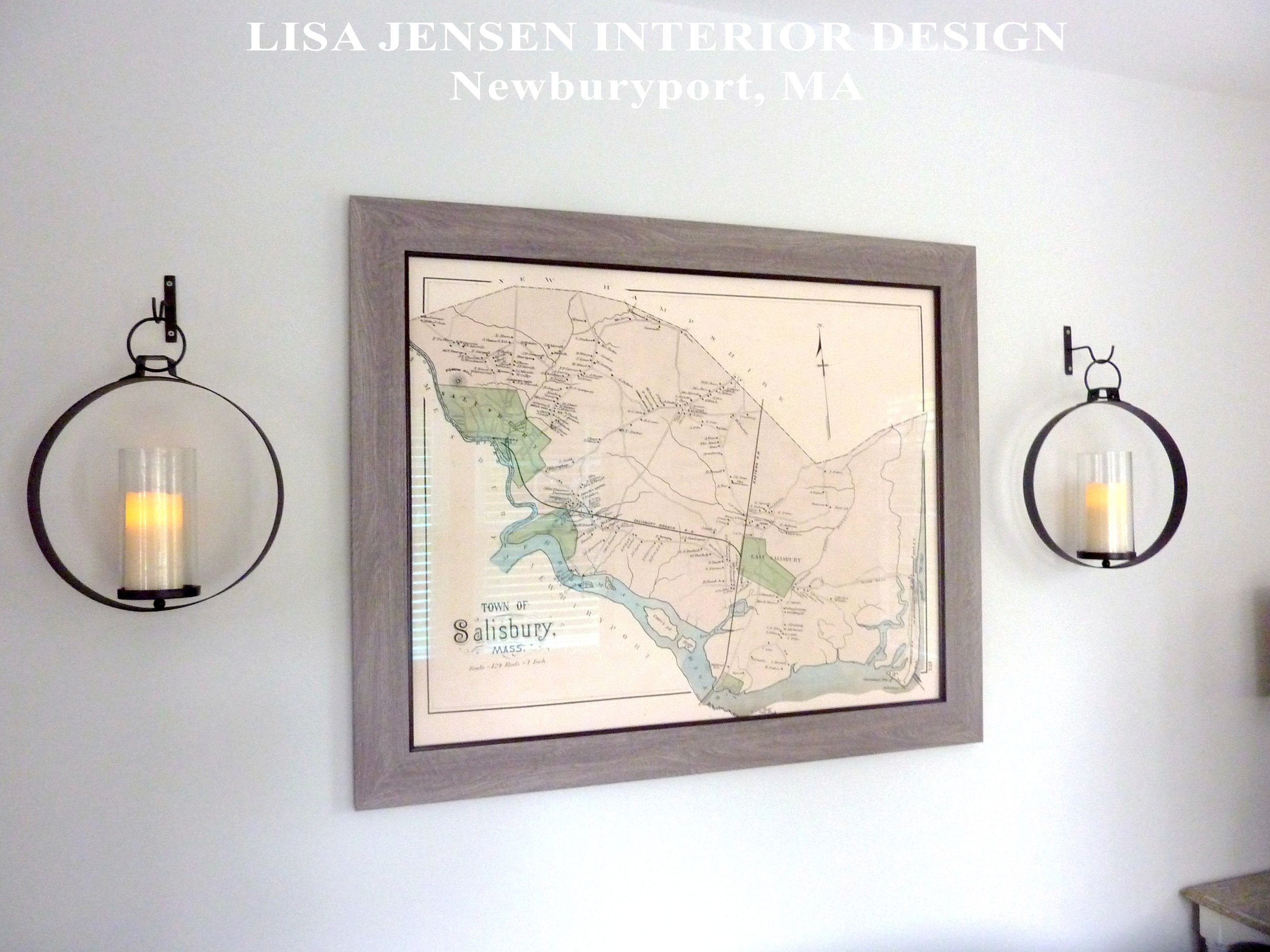 A copy of an old Salisbury Massachusetts map Lisa Jensen found for her clients hangs on the wall in their newly designed Den. The custom framed map is flanked by battery lit candles used with the new forged iron wall sconces.