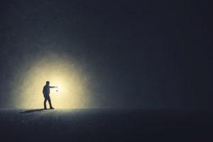 person-walking-with-light-in-dark-300x200.jpg