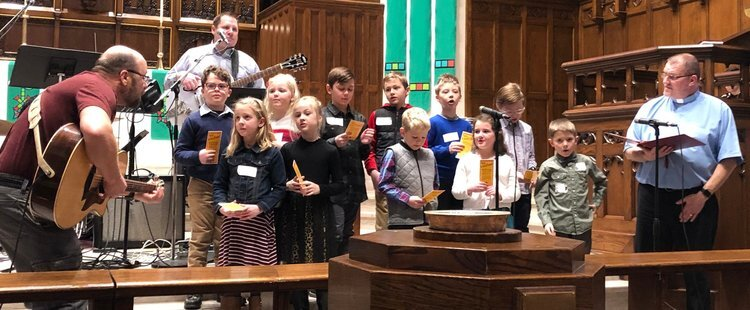Second grade students lead the congregation in a song led by Larry Olson as part of their Confession and Forgiveness milestone