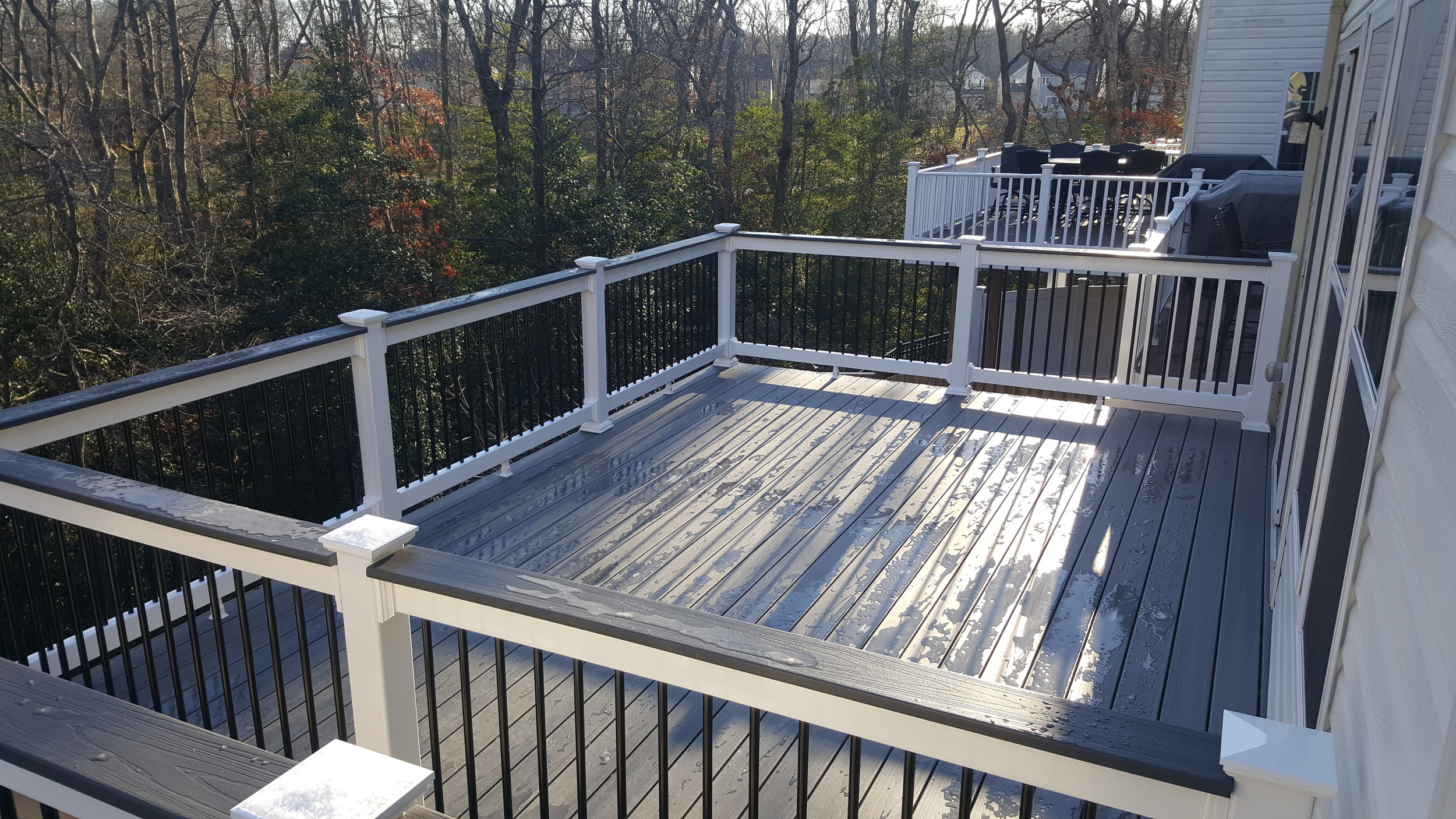 Fiberon Gray Birch decking, Monument rails with Black Aluminum Balusters and Decking toppers. Tiger claw hidden fasteners.