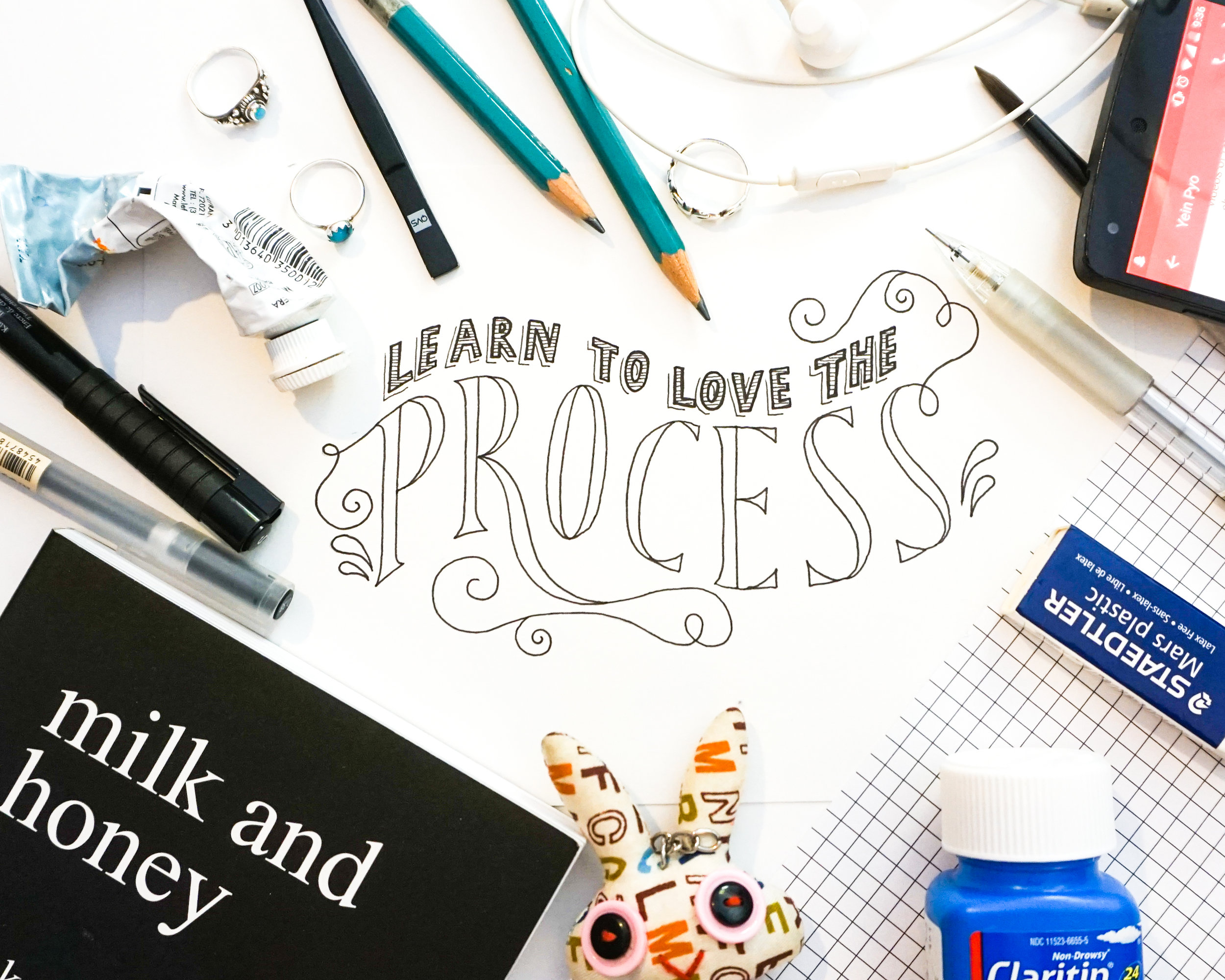 Image: Photograph of my hand lettering surrounded by various objects from my creative process.