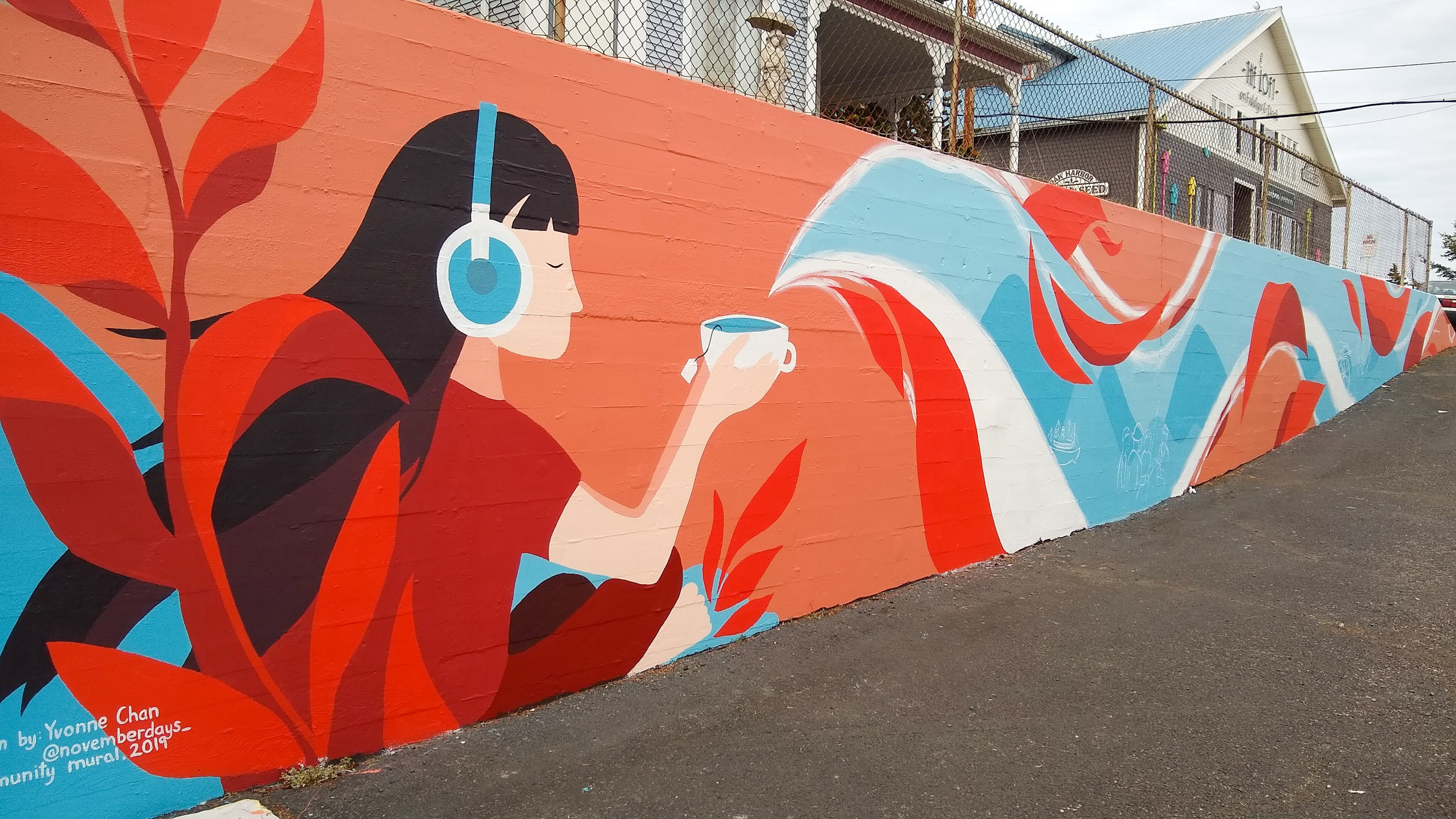 Image Desc: Brightly colored mural depicting a girl listening to headphones and holding a cup of tea, while the rolling steam shows images of early Chinese immigrants arriving on ships and working on farms.