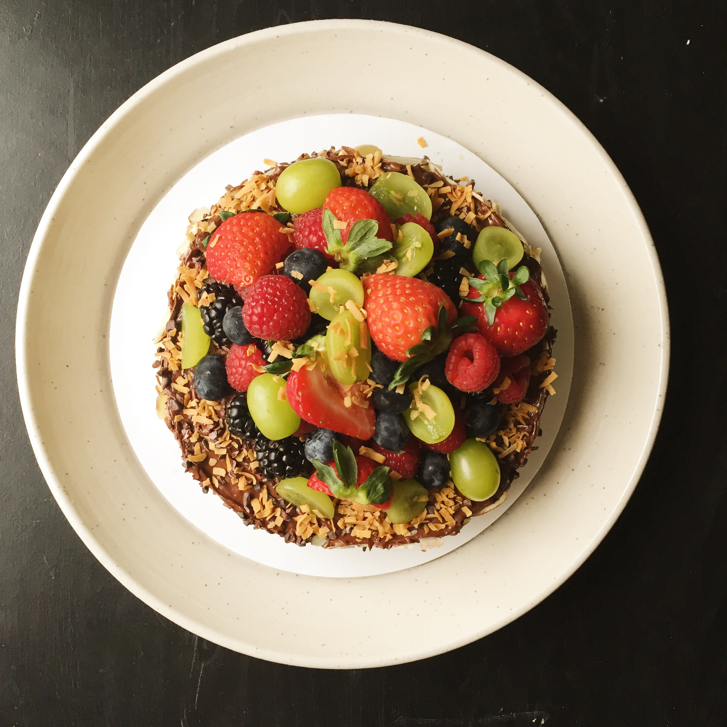 Paleo Chocolate Cake adorned with fruit, toasted coconut, almonds, and cacao nibs.