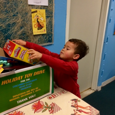 Milo placing a toy he chose in his school's holiday toy drive box. The drive benefited Columbia University's Head Start program.