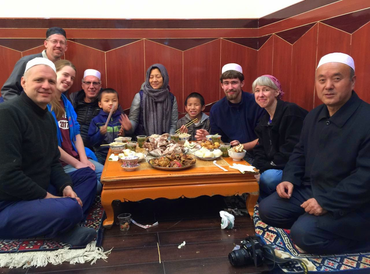 Jodie and her family eating a meal with their Chinese Muslim hosts.