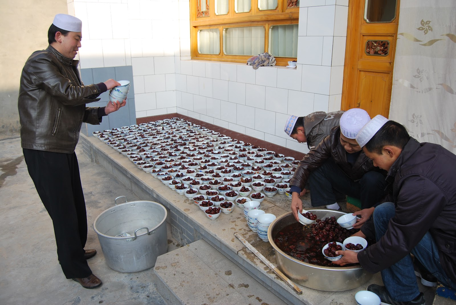 Young men filling bowls of dates