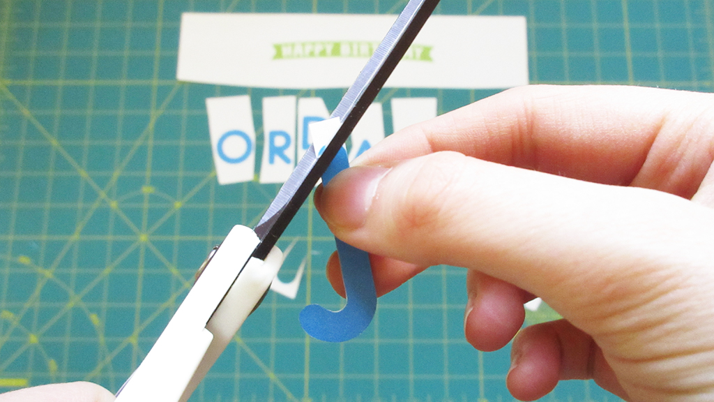 Cutting out the letter J for DIY Streamer Name Cake Topper