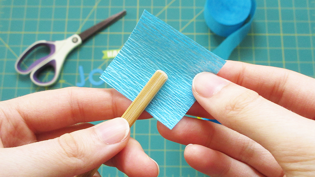 Holding a chopstick and a blue crepe paper square, about to fold it over the chopstick