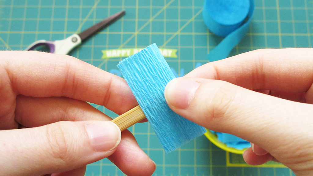 Folding the blue crepe paper square over the chopstick