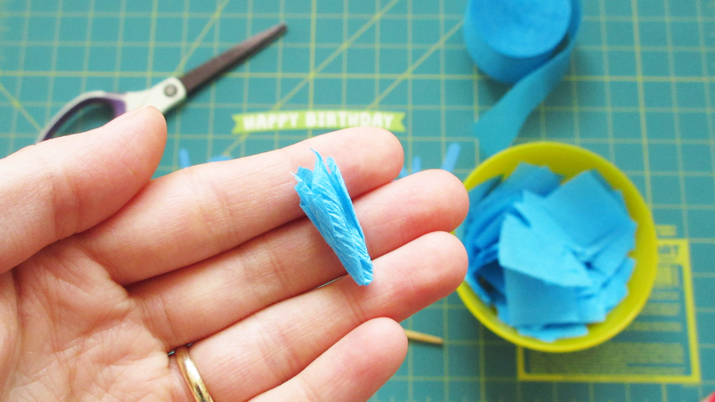 Holding one finished blue crepe paper piece, folded and pinched