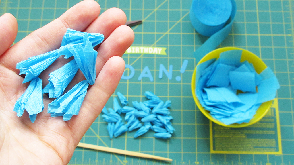 Holding a bunch of finished blue crepe paper pieces in hand with more sitting in the background