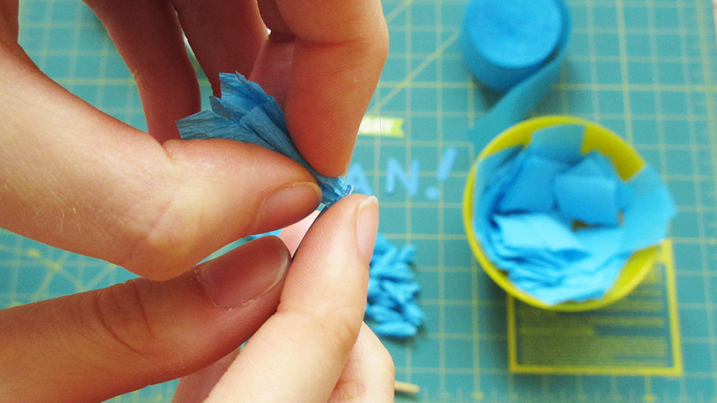 Using hot glue to glue the blue crepe paper piece to the letter J