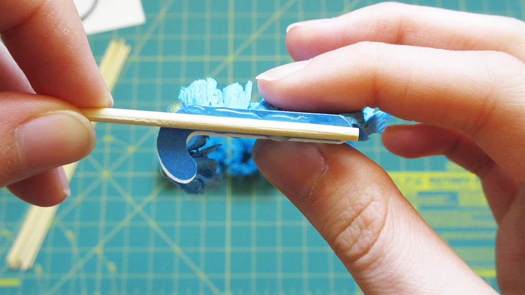 Placing a skewer into the hot glue on the letter J of the DIY Streamer Name Cake Topper