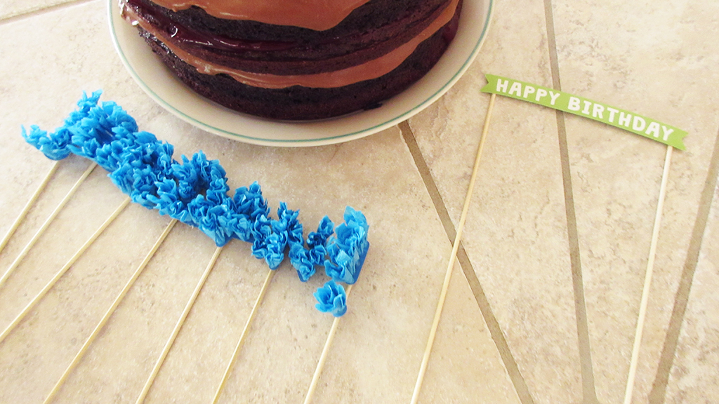 Finished DIY Streamer Name Cake Topper laying on the counter next to chocolate birthday cake, about to be placed
