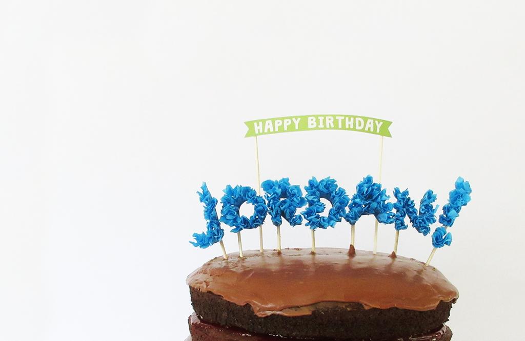DIY Streamer Name Cake Topper placed in chocolate birthday cake