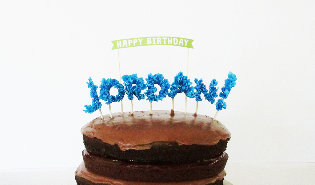 DIY Streamer Name Cake Topper and Happy Birthday Banner on top of chocolate birthday cake