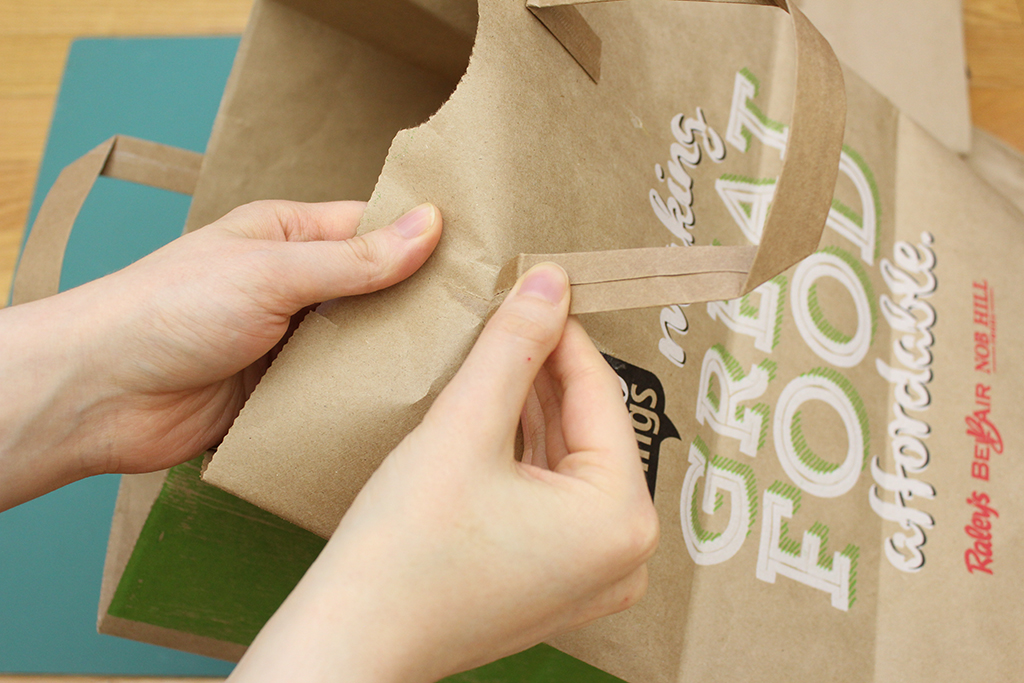 Taking handles off brown paper bag for Christmas Holly Leaf Decoration