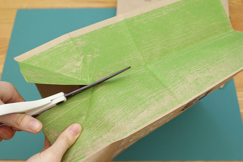 Cutting open the side of the brown paper bag for Christmas Holly Leaf Decoration