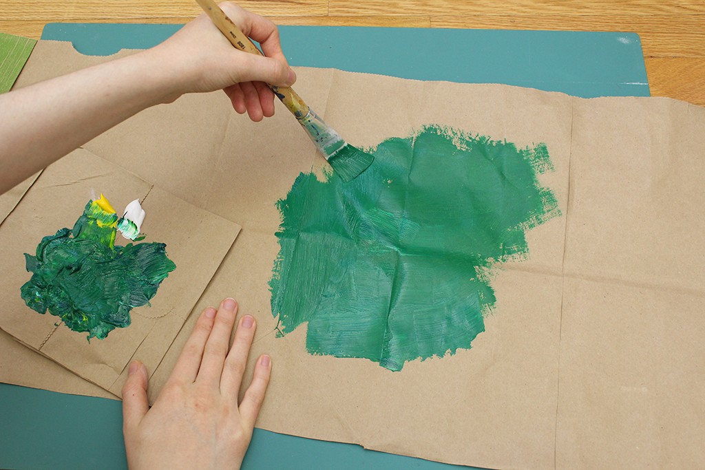 Painting brown paper bag green with acrylic paint for DIY Christmas Holly Leaf Decoration