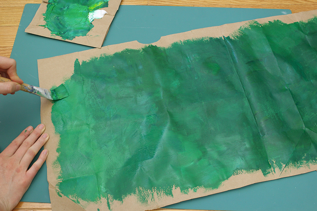 Finishing painting brown paper bag for DIY Holly Leaf Decoration