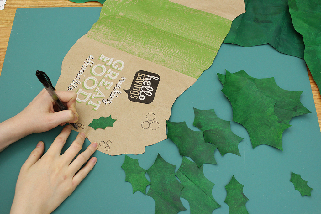 Drawing circles on the red painted brown paper bag for the berries