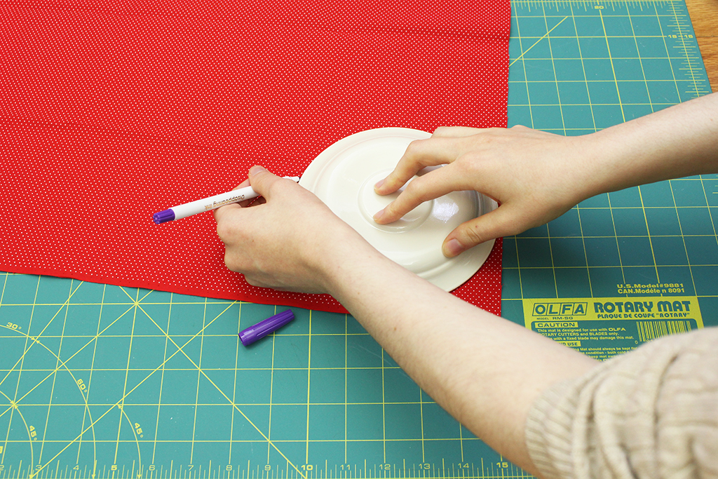 Tracing around a plate on the polka-dot fabric to decorate cocoa mix jar
