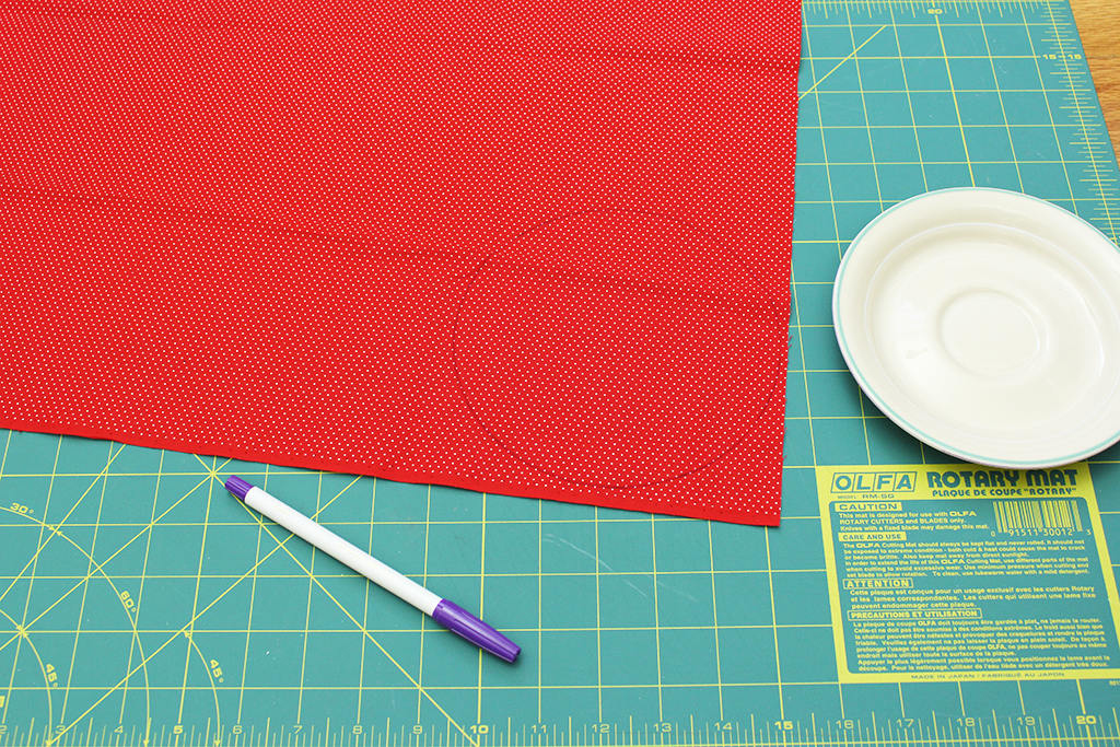 Circle traced onto polka-dot fabric with fabric pen ready to be cut out