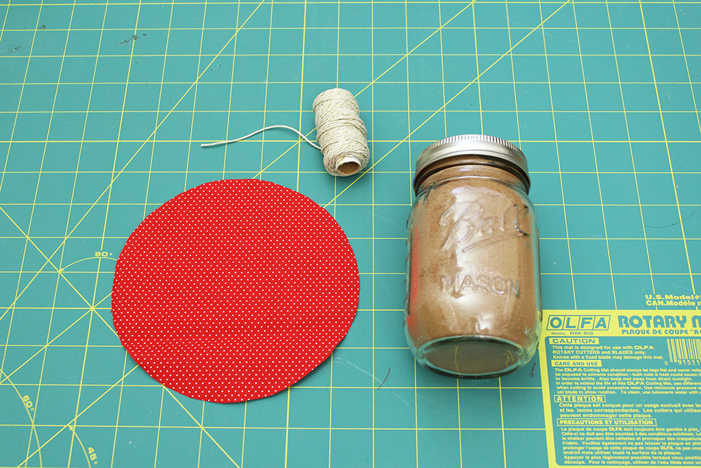 Cut out circle, hemp twine, and jar of Vegan Candy Cane Cocoa Mix laying on cutting mat