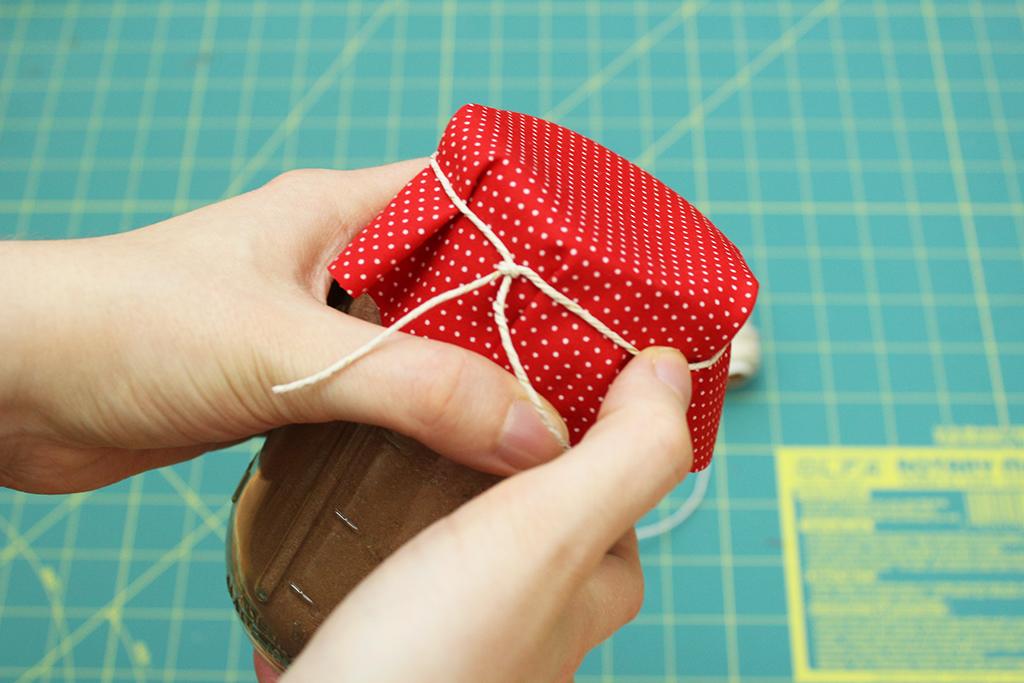 Decorating Vegan Candy Cane Cocoa Mix jar with polka-dot fabric and hemp twine