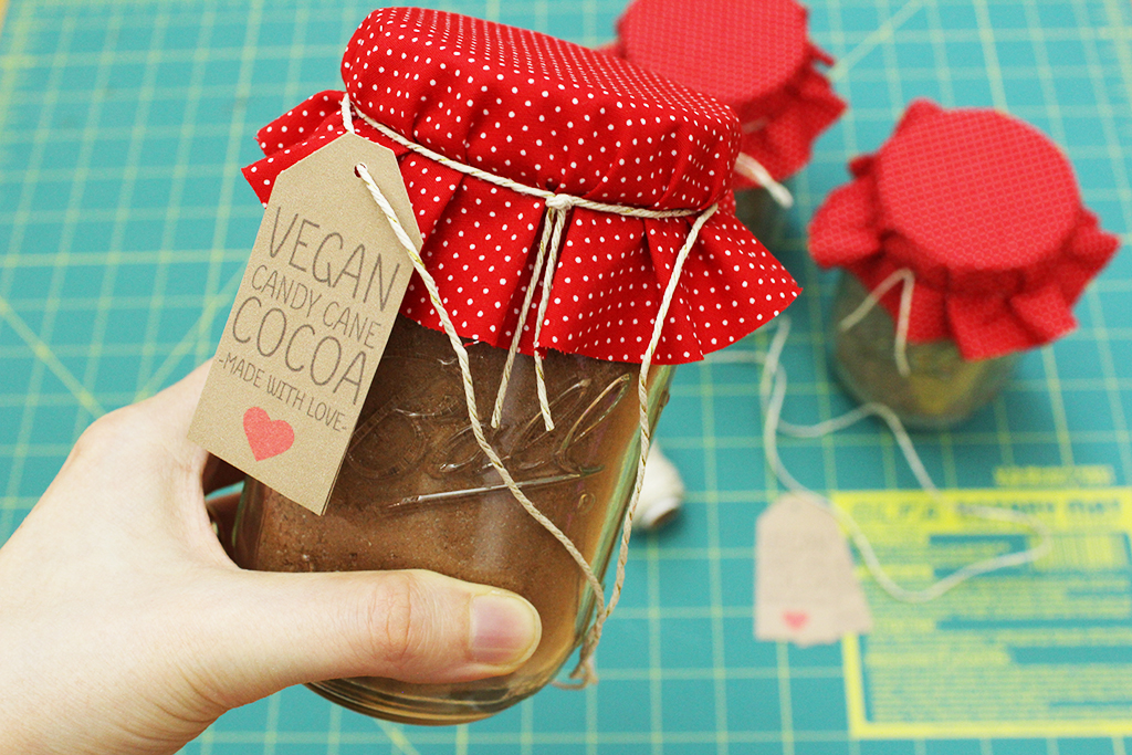 Holding Vegan Candy Cane Cocoa Mix jar, about to tie bow