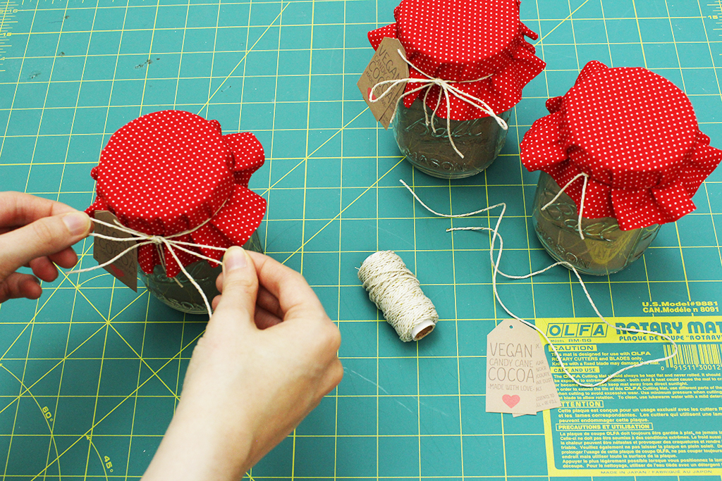 Tying final bow on Vegan Candy Cane Cocoa Mix jar