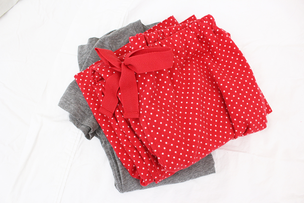 Red and white polka-dot pajama bottoms sitting on bed