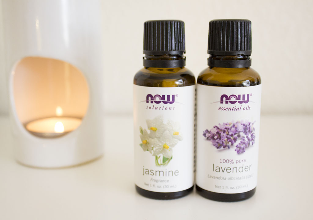 Lavender and jasmine essential oils with oil burner burning in the background